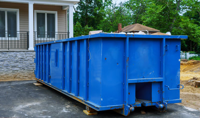 A blue large dumpster in front of a house.