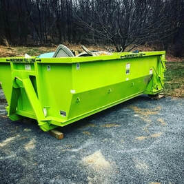 A green dumpster in the woods.