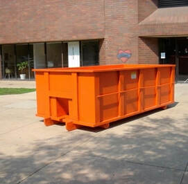 An orange dumpster in front of an office building.