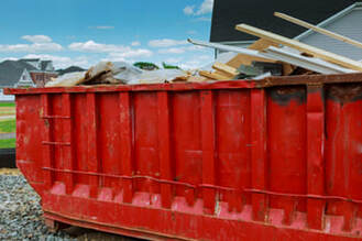 Red dumpster filled with debris